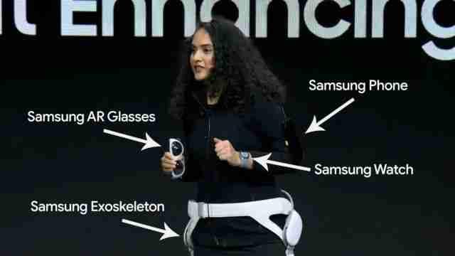 三星的工作人员将 AR 眼镜与挂在手臂上的手机相连